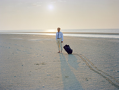 Man on beach with rolling suitcase - p1207m1109473 by Michael Heissner