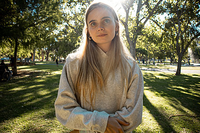 Teenage girl with blond hair in a park - p1640m2258514 by Holly & John