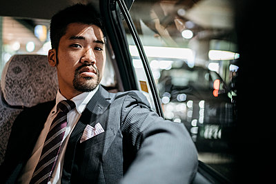 Portrait of confident young businessman in a taxi - p300m2140136 by Juri Pozzi