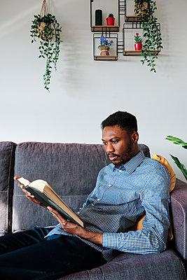 Man reading book while sitting on sofa at home - p300m2273650 by Alvaro Gonzalez