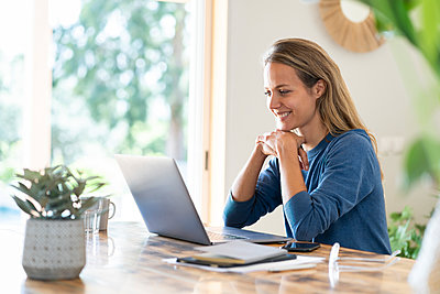 Smiling female entrepreneur looking at laptop while sitting at table - p300m2277610 by Steve Brookland