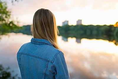 Sweden, Stockholm, Liljeholmen, Teenage girl (16-17) standing at edge of lake - p352m1126668f by Åke Nyqvist