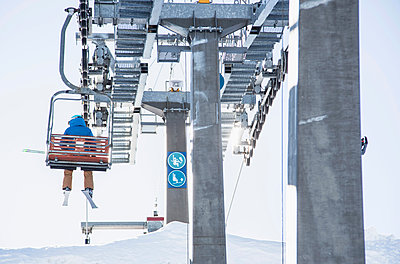 Skier on ski lift, rear view - p429m1519422 by Guido Cavallini