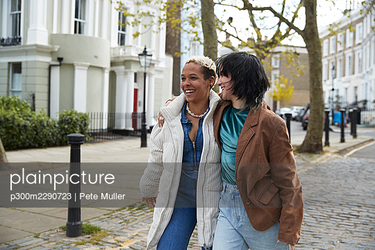 Happy lesbian couple walking with arm around on footpath - p300m2290723 by Pete Muller