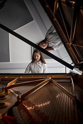 Adorable schoolgirl playing piano in music school - p1315m2003043 by Wavebreak
