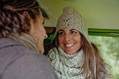 Smiling woman talking with man in camper van during road trip - p300m2250218 by LOUIS CHRISTIAN