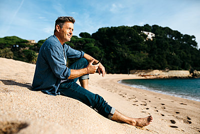 Smiling man with smart phone sitting at beach against hill during sunny day - p300m2252972 by Josep Rovirosa