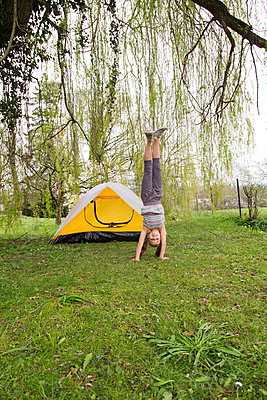 Smiling girl doing a handstand in garden - p429m954489f by Stefanie Grewel