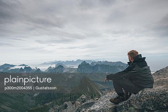 Norway, Lofoten, Moskenesoy, Young man sitting at Hermannsdalstinden, looking over Kjerkefjord - p300m2004355 von Gustafsson