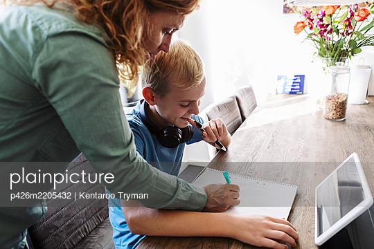Mother helping smiling son in studying at home - p426m2205432 by Kentaroo Tryman