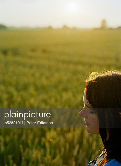 Mid adult woman in fields - p5282101f by Peter Eriksson