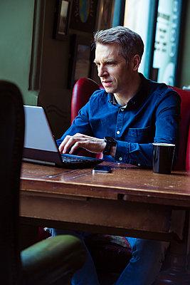 Mann in einem Cafe arbeitet am Laptop  - p1057m1526438 von Stephen Shepherd