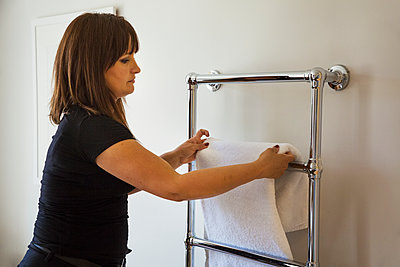 Woman standing in a bathroom, hanging fresh towel over metal towel holder. - p1100m1490048 by Mint Images