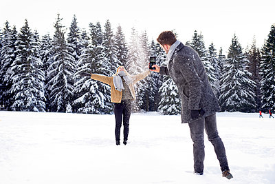 Young couple having a snowball fight - p1124m1589328 by Willing-Holtz
