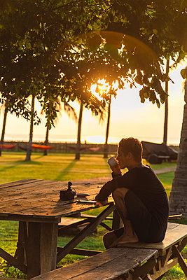Young man drinking tea at outdoor table, Sumbawa, Indonesia - p1166m2202341 by Konstantin Trubavin