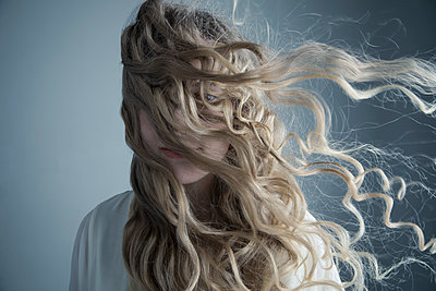 Portrait wind blowing long curly blonde hair across face of Caucasian young woman - p1192m1213244 by Hero Images