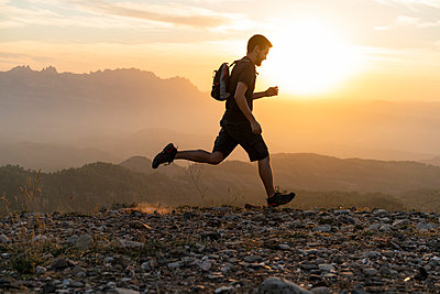 Spain, Barcelona, Natural Park of Sant Llorenc, man running in the mountains at sunset - p300m2058576 von VITTA GALLERY