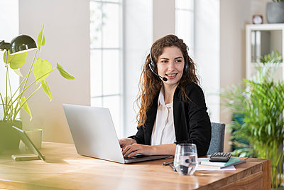 Smiling female customer service representative with headphones looking away while sitting in front of laptop at desk - p300m2276473 by Steve Brookland