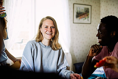 Portrait of smiling young woman enjoying social gathering with friends at home - p426m2117245 by Maskot