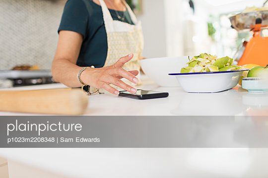 Woman with smart phone baking at kitchen counter - p1023m2208348 by Sam Edwards