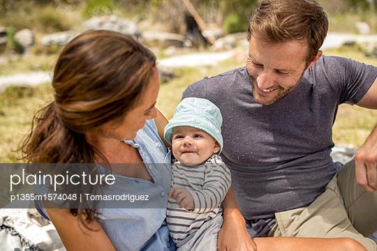 Familie mit Baby entspannt sich am Seeufer - p1355m1574048 von Tomasrodriguez