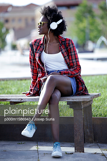 Portrait of young woman sitting on bench in city park listening music with headphones - p300m1586943 von Josep Suria