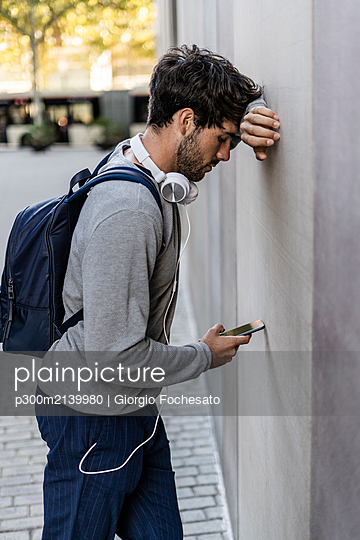 Man leaning against a wall checking cell phone - p300m2139980 by Giorgio Fochesato