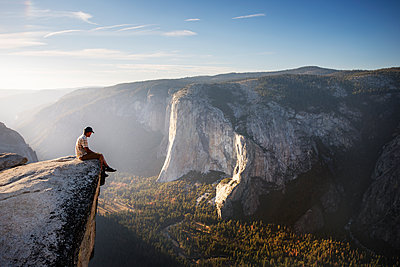 Hiker sitting on rock while watching mountains at Yosemite National Park against sky - p1166m1085964f by Cavan Images