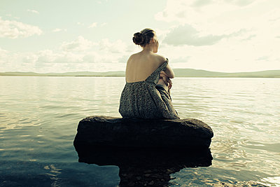Rear view of thoughtful woman sitting on rock in river against cloudy sky - p1166m1489846 by Cavan Images
