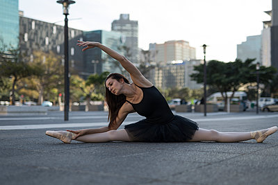 Female ballet dancer stretching before dancing in the city street - p1315m2014517 by Wavebreak