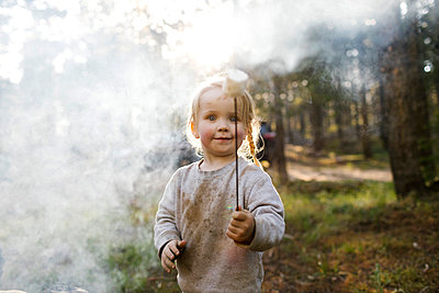 Portrait of girl (2-3) holding marshmallow near campfire in forest, Wasatch Cache National Forest - p1427m2213545 by Jessica Peterson