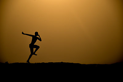 Silhouette of a dancing man at night - p1695m2290935 by Dusica Paripovic