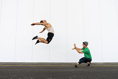 Two acrobats doing tricks together, jumping mid-air - p300m2012363 von VITTA GALLERY