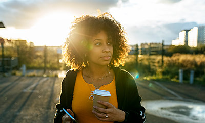 Young woman with afro hair holding coffee and smart phone looking away against sky - p300m2243845 by Marco Govel