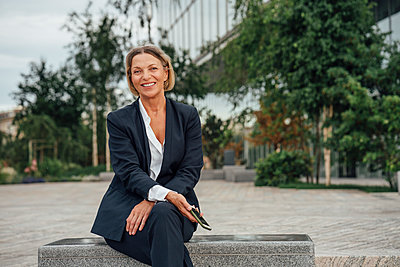 Smiling mature female professional with mobile phone sitting on bench - p300m2294219 by Vasily Pindyurin