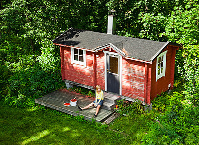 Gilr outside small red house - p4265604f by Tuomas Marttila
