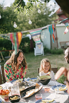 Happy family having lunch at table in backyard during garden party - p426m2036568 by Maskot