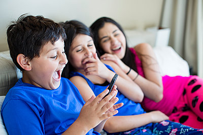 Hispanic siblings using cell phone on sofa - p555m1412049 by Deborah Kolb