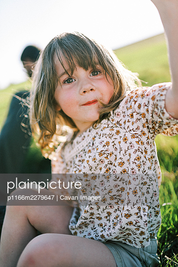 Little happy girl sitting on a hill smiling and touching camera - p1166m2279647 by Cavan Images