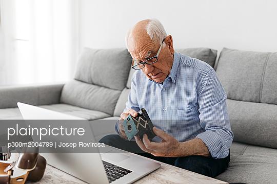Senior man using laptop and holding his old photo camera - p300m2004799 von Josep Rovirosa