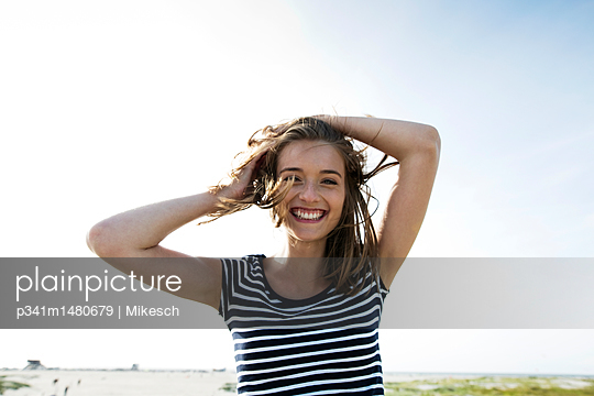 Happy young woman on St. Peter Ording beach  - p341m1480679 by Mikesch