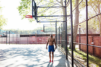 Man looking up while standing in basket ball court - p1166m1164488 by Cavan Images