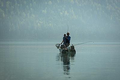 Two fishermen fishing in the river - p1315m2055876 by Wavebreak