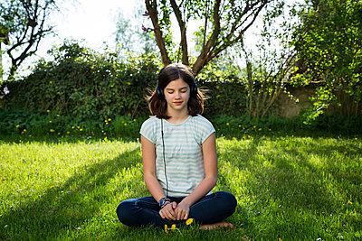 Girl sitting on meadow listening music with headphones - p300m1588204 by Larissa Veronesi