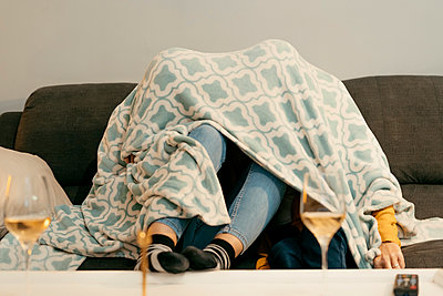 Mother and daughter hiding under blanket on sofa in living room at home - p300m2240457 by Eloisa Ramos