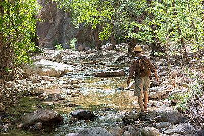 Caucasian man hiking along rocky creek - p555m1453230 by Marc Romanelli