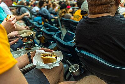Man sitting in stadium eating hot dog - p555m1504046 by Steve Prezant