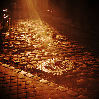 Sunbeams shed light on cobbled street  - p567m1095620 by Alexis Bastin