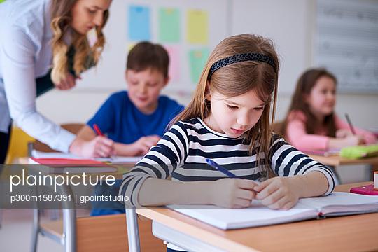 Schoolgirl writing in exercise book in class - p300m1587391 von gpointstudio