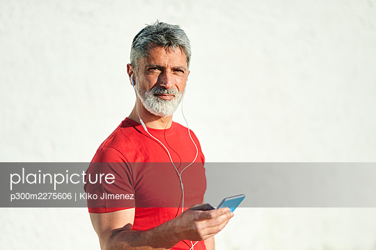 Handsome man with smart phone by wall during sunny day - p300m2275606 by Kiko Jimenez
